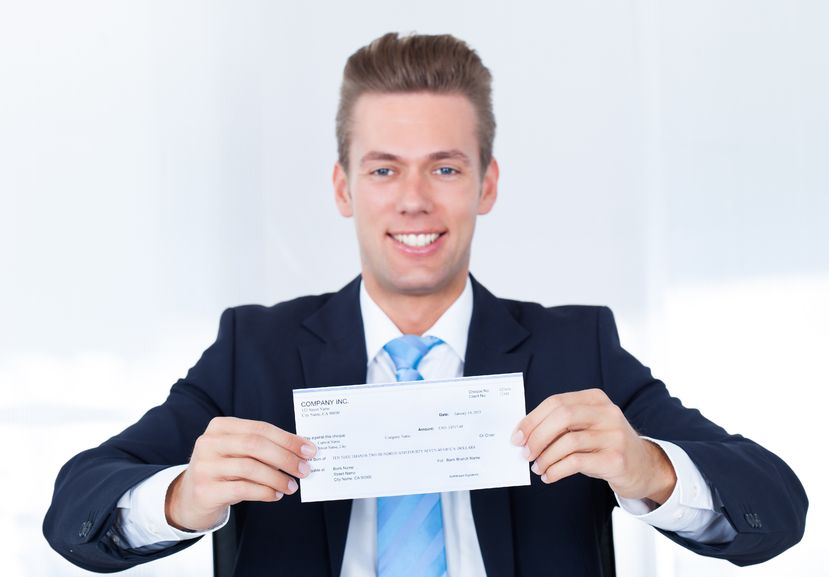21254254 - portrait of young happy businessman offering cheque